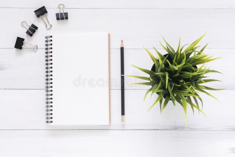 Fundo de madeira branco da tabela da mesa de escritório com zombaria aberta acima dos cadernos e as penas e a planta imagens de stock
