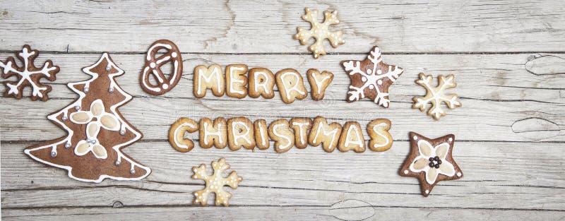 Fundo de madeira cinzento de Christmassy com pão-de-espécie e letra alegre do ` s de Christma fotografia de stock