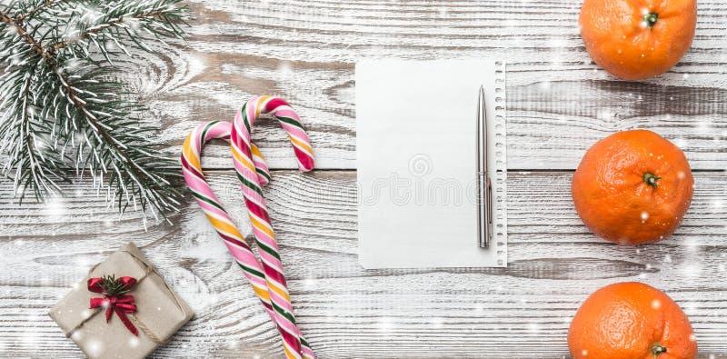 Fundo de madeira com flocos de neve Cartão do inverno Verde do abeto Laranjas Presente Doces coloridos Espaço para rotular para S foto de stock