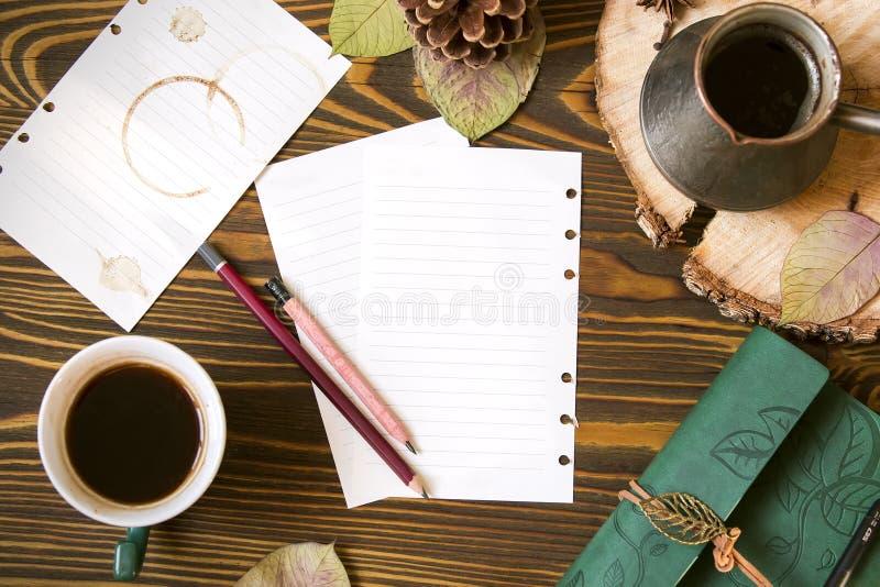 Fundo de madeira com papel para notas, leiteria, cofee, ezve do  de Ñ, cone, folhas de outono Opinião superior do local de traba foto de stock royalty free