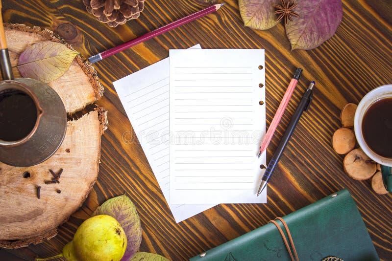 Fundo de madeira com papel para notas, leiteria, cofee, ezve do  de Ñ, folhas de outono Opinião superior do local de trabalho imagem de stock royalty free