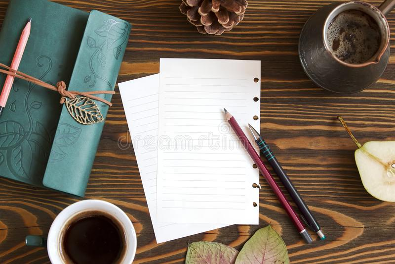Fundo de madeira com placa para notas, leiteria, folhas de outono do cofee Opinião superior do local de trabalho fotografia de stock