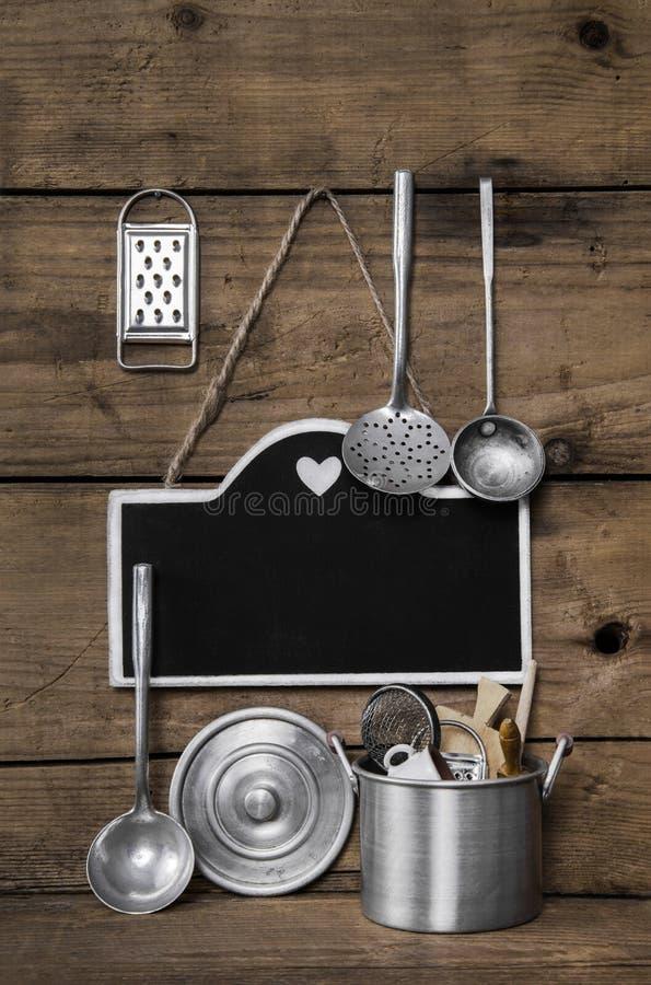 Fundo de madeira da cozinha do vintage com kitchenware velho, blackboa imagens de stock