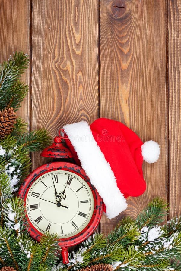 Fundo de madeira do Natal com pulso de disparo, árvore de abeto e chapéu de Santa imagens de stock