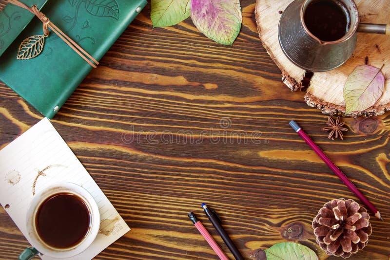 Fundo de madeira do outono vazio com o quadro que consiste na leiteria, cofee, ezve do  de Ñ, cone, folhas de outono, pena Lápis fotografia de stock