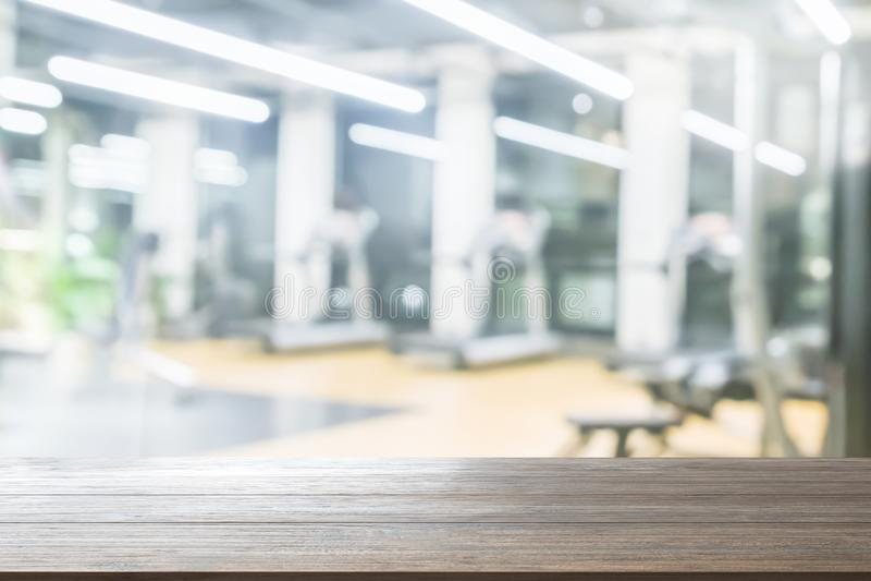 Fundo de madeira do tampo da mesa no fundo borrado do sumário do gym da aptidão de equipamentos do exercício para a composição do imagens de stock