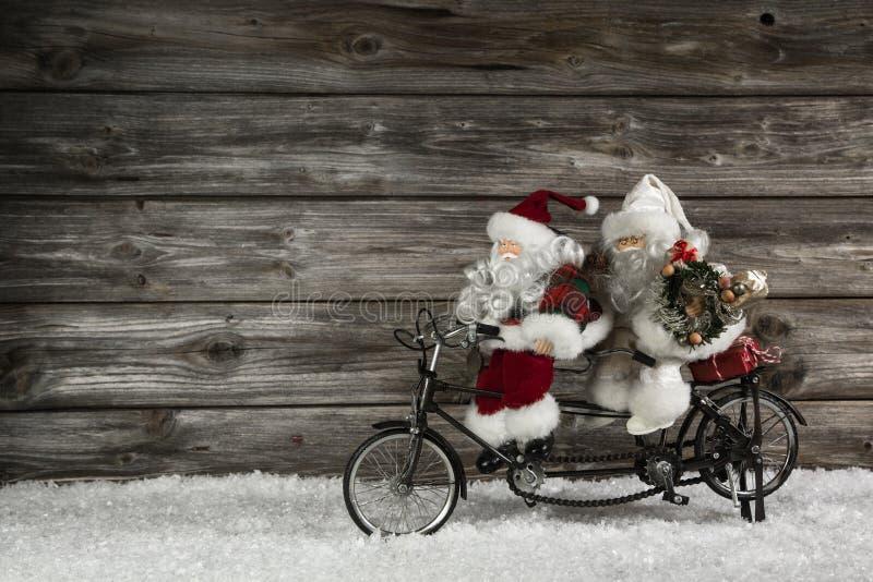 Fundo de madeira engraçado do Natal com dois Papai Noel em um bicy foto de stock