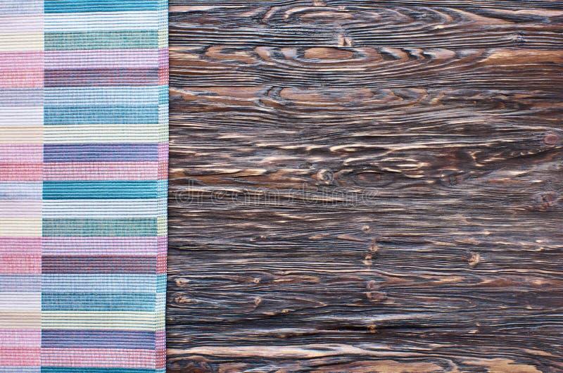 Fundo de madeira escuro velho Tabela de madeira com a toalha de cozinha colorida fotos de stock royalty free