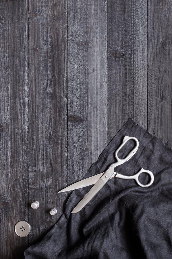 Fundo de madeira preto da costura com tela e tesouras imagens de stock