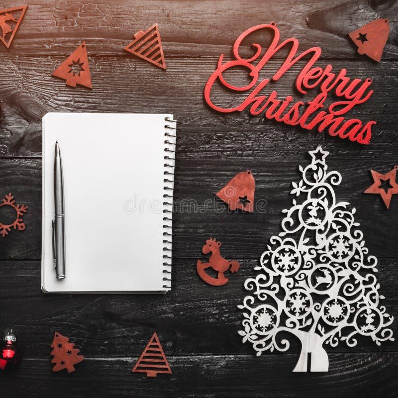 Fundo de madeira preto Feliz Natal inscrição, cartão do cartão, brinquedos de madeira imagem de stock