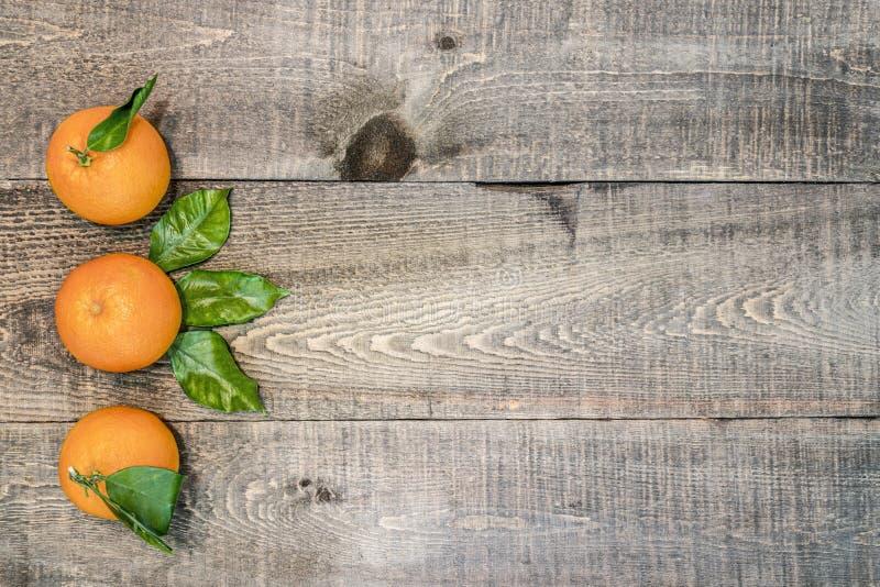 Fundo de madeira rústico com as três laranjas frescas com as folhas imagem de stock