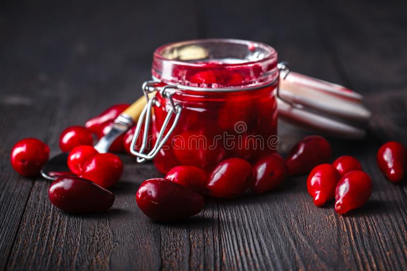 Fundo de madeira velho vermelho maduro Autumn Harvest Wild Berries de Cornel Berries Small Glass Jar fotos de stock royalty free