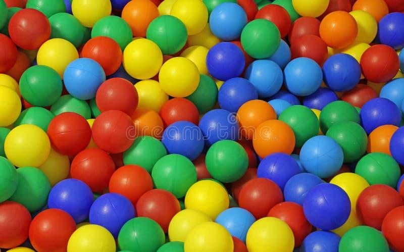 Fundo de muitas bolas plásticas coloridas em uma associação imagens de stock