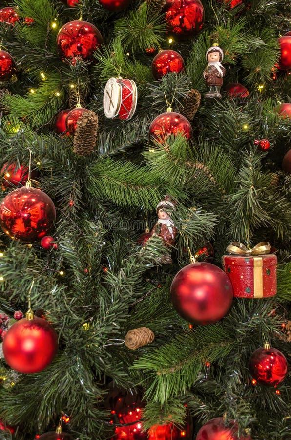 Fundo de ramos naturais e artificiais do pinho com as estatuetas velhas das decorações do Natal, os cones e as bolas vermelhas fotografia de stock