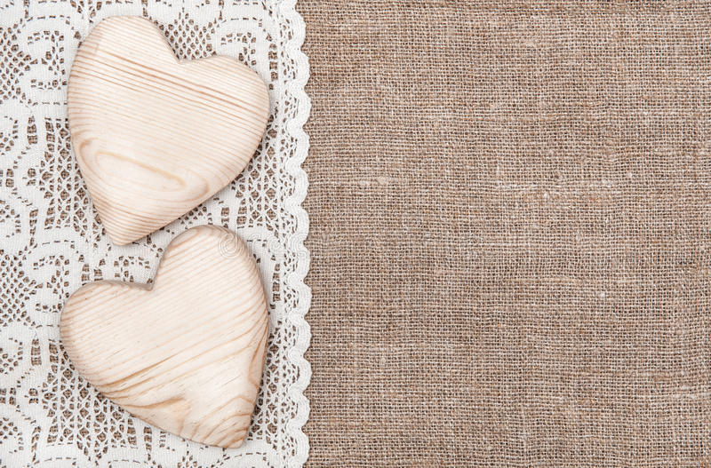 Fundo de serapilheira com pano laçado e corações de madeira fotos de stock