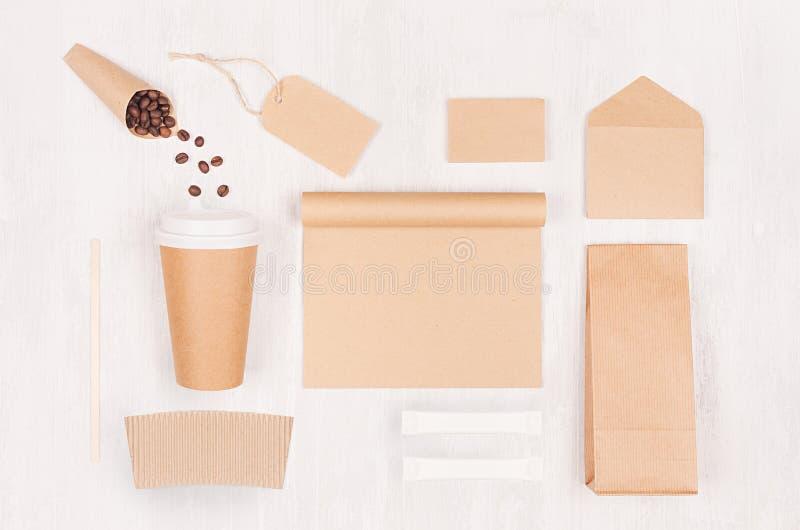 Fundo decorativo para o restaurante e a cafetaria - copo de papel vazio, caderno, etiqueta, pacote, feijões de café, açúcar na ma fotografia de stock