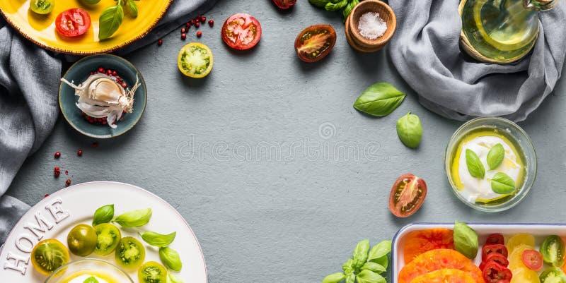 Fundo do alimento com os tomates coloridos frescos, o mozzarella com óleo de azeitonas e as folhas da manjericão na mesa de cozin imagens de stock royalty free