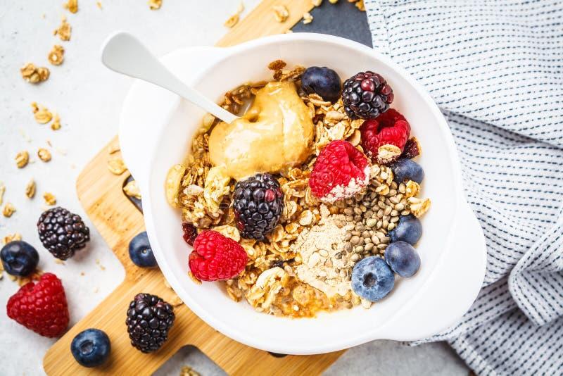 Fundo do alimento de café da manhã Granola com sementes de cânhamo, pó do maca, manteiga de amendoim e bagas na tabela branca imagem de stock