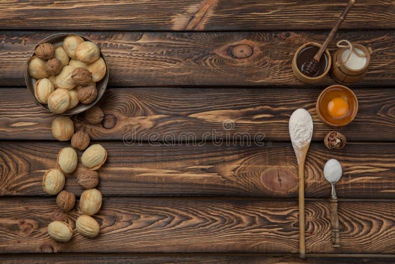 Fundo do alimento Os ingredientes do cozimento flour, ovos, porcas, açúcar, frutos secados na tabela de madeira Vista superior Co imagens de stock