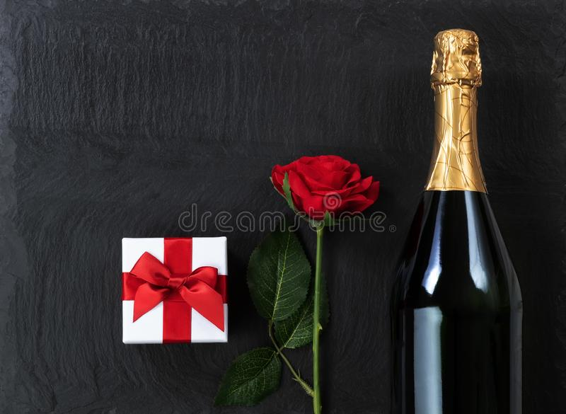 Fundo do aniversário com champanhe e presentes na pedra natural da ardósia imagem de stock
