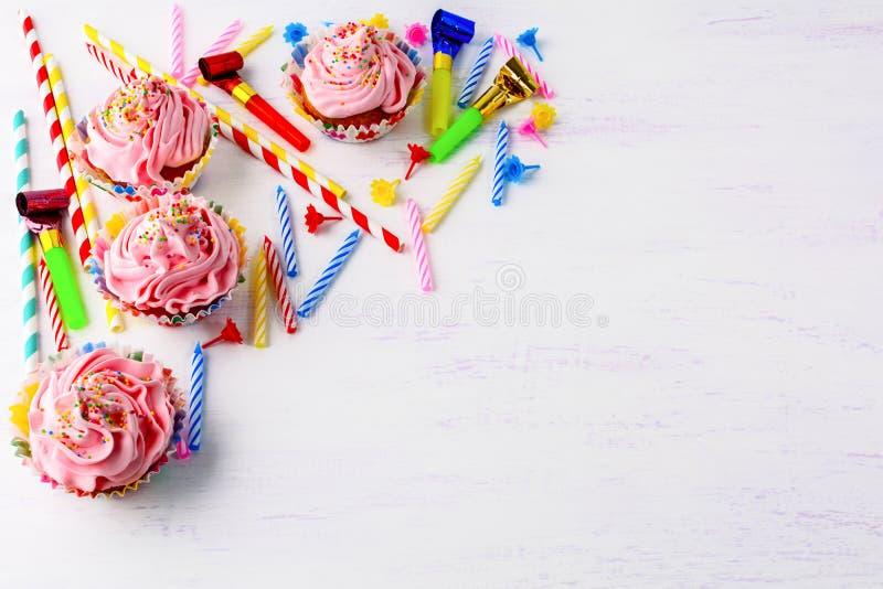 Fundo do aniversário com queques cor-de-rosa fotografia de stock royalty free