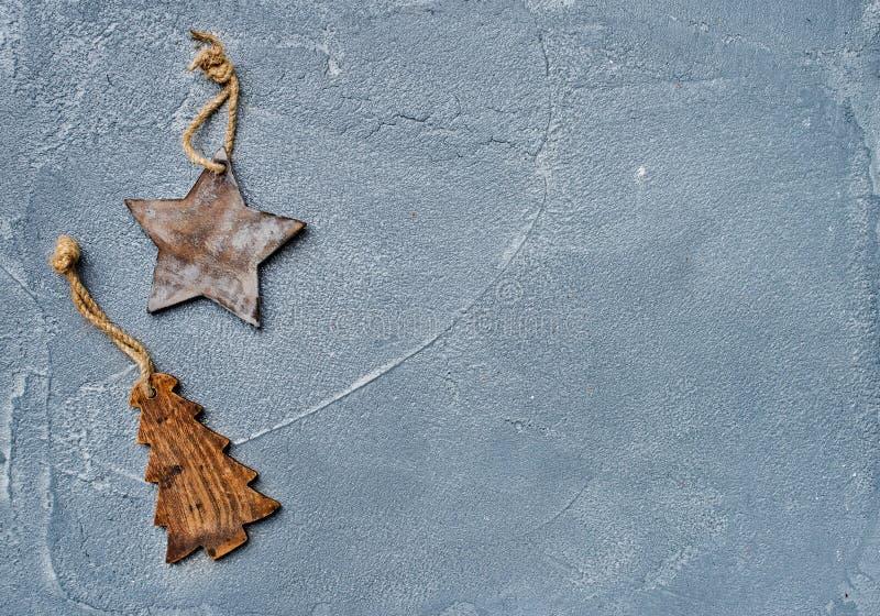 Fundo do ano novo ou do Natal Brinque a árvore de madeira rústica da estrela e da pele sobre a superfície do cinza do grunge, vis fotos de stock