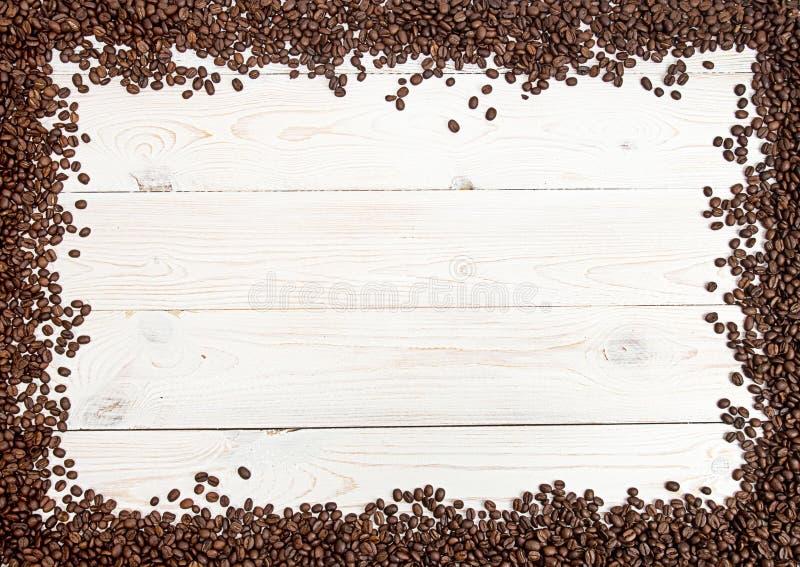 Fundo do café Os feijões de café espalharam na tabela em quatro lados fotografia de stock royalty free