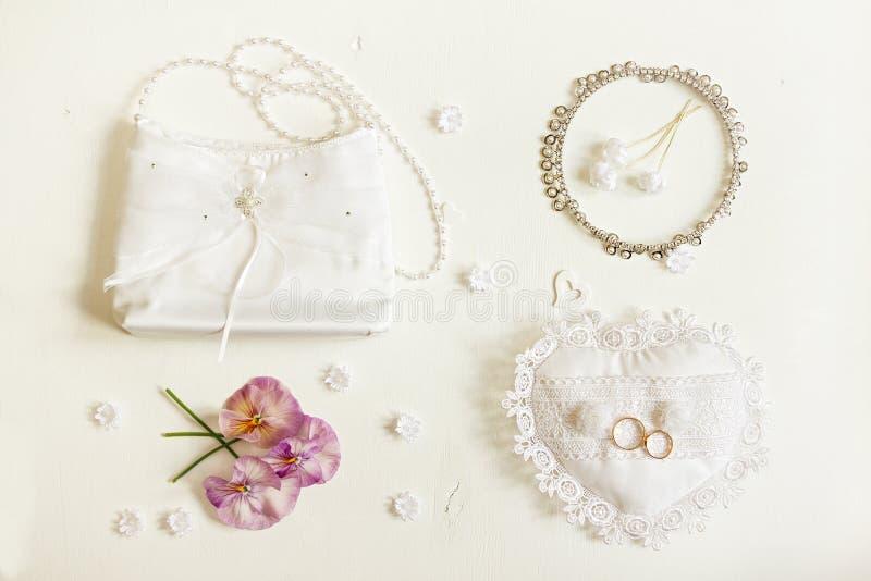 Fundo do casamento Acessórios da noiva: anéis, bolsa, boutonnie fotos de stock royalty free