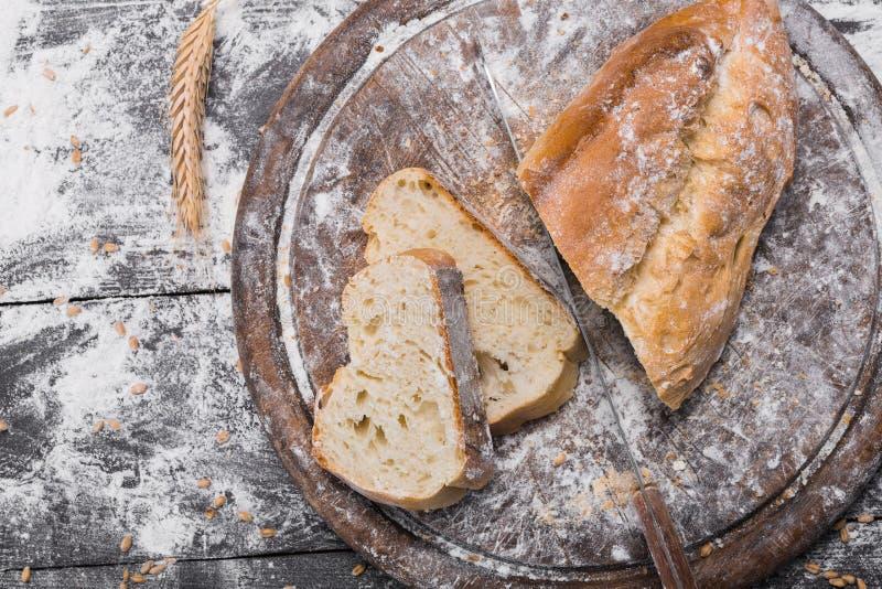 Fundo do conceito da padaria Pão e faca cortados branco fotografia de stock
