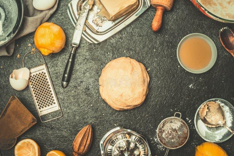 Fundo do cozimento com massa, pedágios da cozinha e ingredientes: Farinha, ovos, manteiga no fundo rústico escuro fotografia de stock royalty free