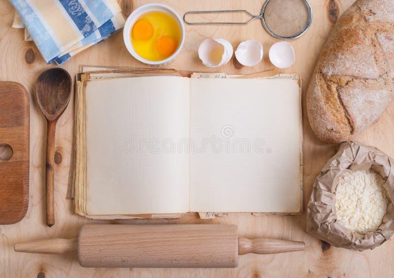 Fundo do cozimento com o livro vazio do cozinheiro, casca de ovo, farinha, rolamento fotografia de stock