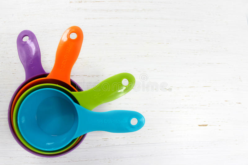 Fundo do cozimento com os copos de medição coloridos brilhantes em w rústico imagens de stock royalty free