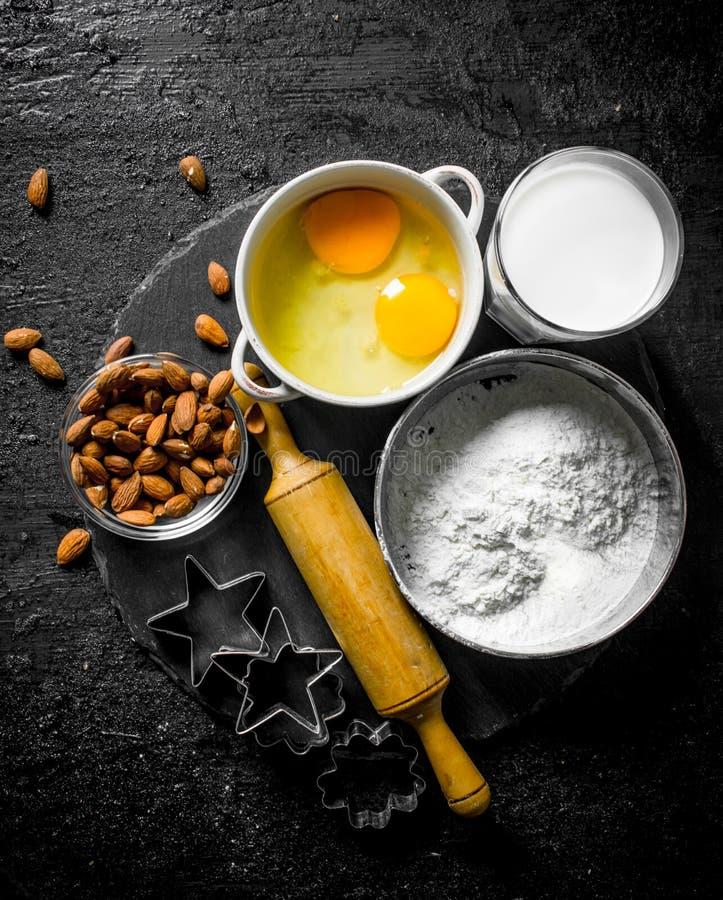 Fundo do cozimento Farinha com leite, amêndoas e formulários para cookies de cozimento fotos de stock royalty free
