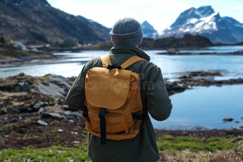 Fundo do curso e da aventura, caminhante com trouxa que aprecia a paisagem em Lofoten, Noruega imagens de stock royalty free