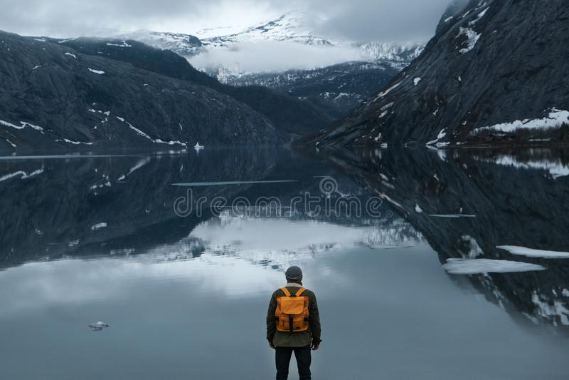 Fundo do curso e da aventura, caminhante com trouxa que aprecia a paisagem em Lofoten, Noruega fotos de stock