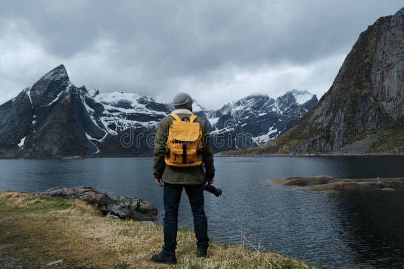 Fundo do curso e da aventura, caminhante com trouxa que aprecia a paisagem em Lofoten, Noruega fotos de stock royalty free