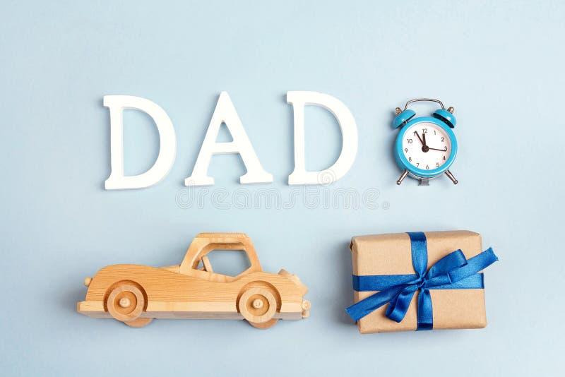 Fundo do dia de pais com o carro de madeira do brinquedo, caixa de presente, cloc do alarme fotos de stock royalty free