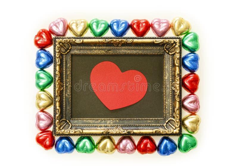 Fundo do dia de Valentim com forma colorida do coração dos chocolates e quadro do ouro da vista superior fotos de stock royalty free
