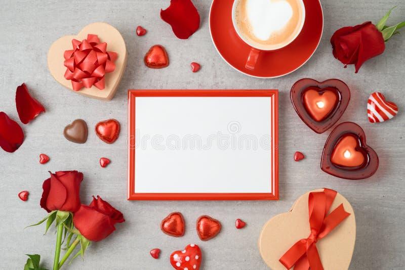 Fundo do dia de Valentim com quadro da foto, copo de café, chocolate da forma do coração, velas e caixas de presente imagens de stock royalty free