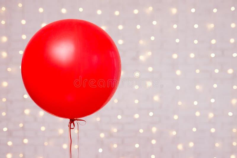 Fundo do dia de Valentim - espaço vermelho grande do balão e da cópia sobre a parede de tijolo branca fotografia de stock royalty free