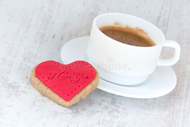 Fundo do dia de Valentim Um coração deu forma à cookie e a uma xícara de café sobre um fundo rústico de madeira branco foto de stock royalty free