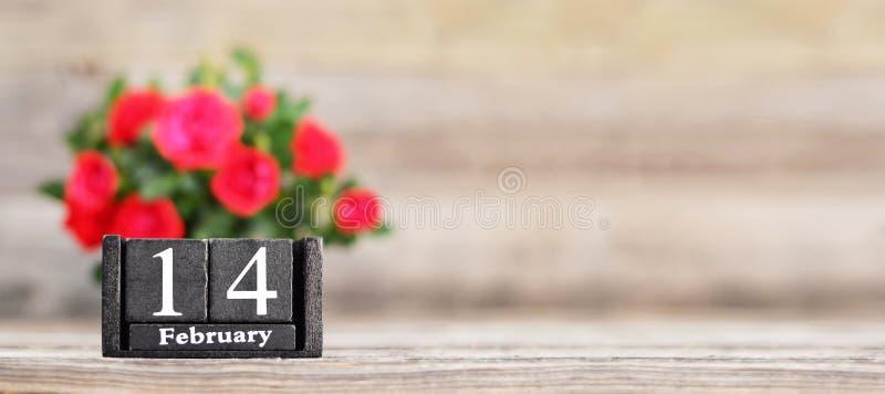 Fundo do dia dos namorados com rosas vermelhas e retro-calendário de madeira fotos de stock royalty free