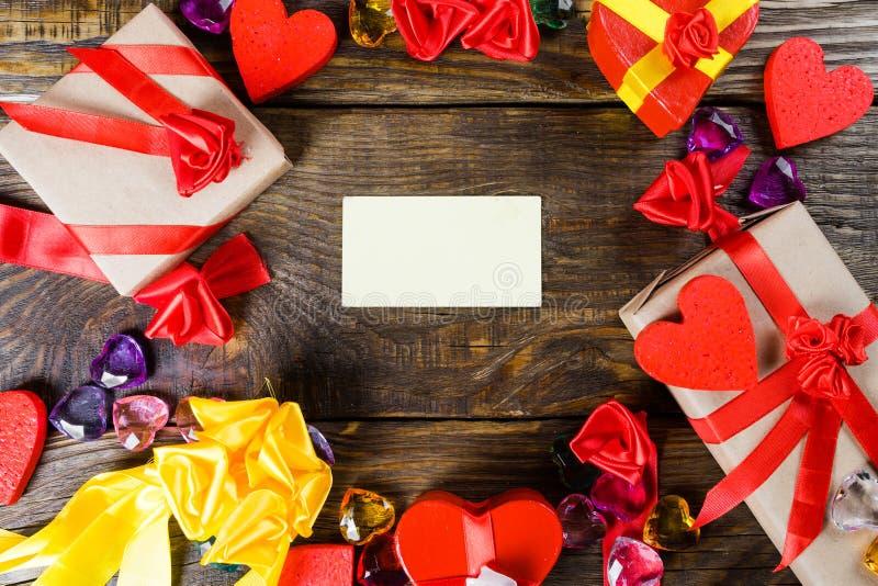 Fundo do dia do ` s do Valentim com cartão de cumprimentos, decorações dos corações e os presentes pequenos na tabela de madeira  fotos de stock royalty free