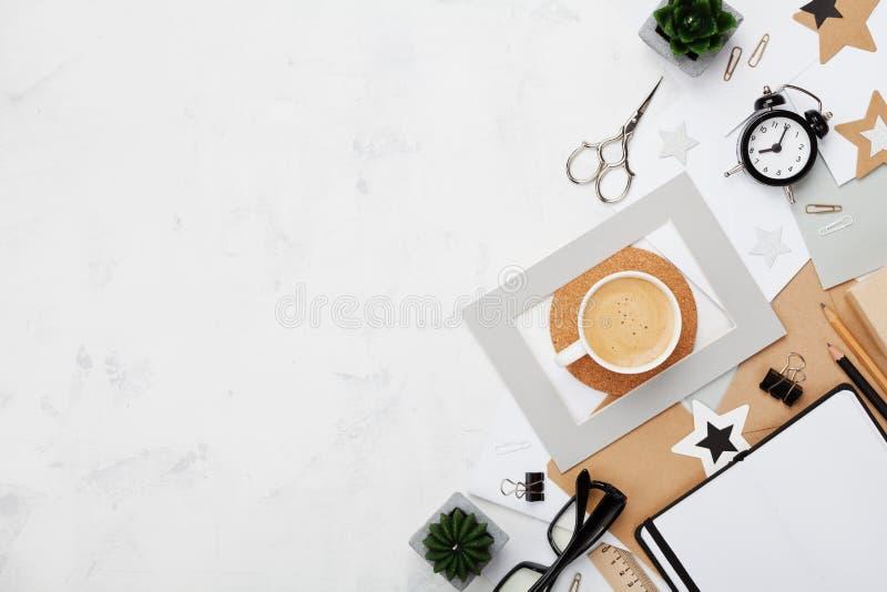 Fundo do espaço de trabalho do blogger da forma Café, material de escritório, alarme e caderno limpo na opinião branca do desktop fotografia de stock