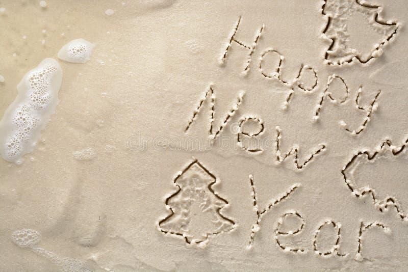 Fundo do feriado - ano novo feliz e árvore de Natal, escrita em um Sandy Beach tropical fotografia de stock royalty free