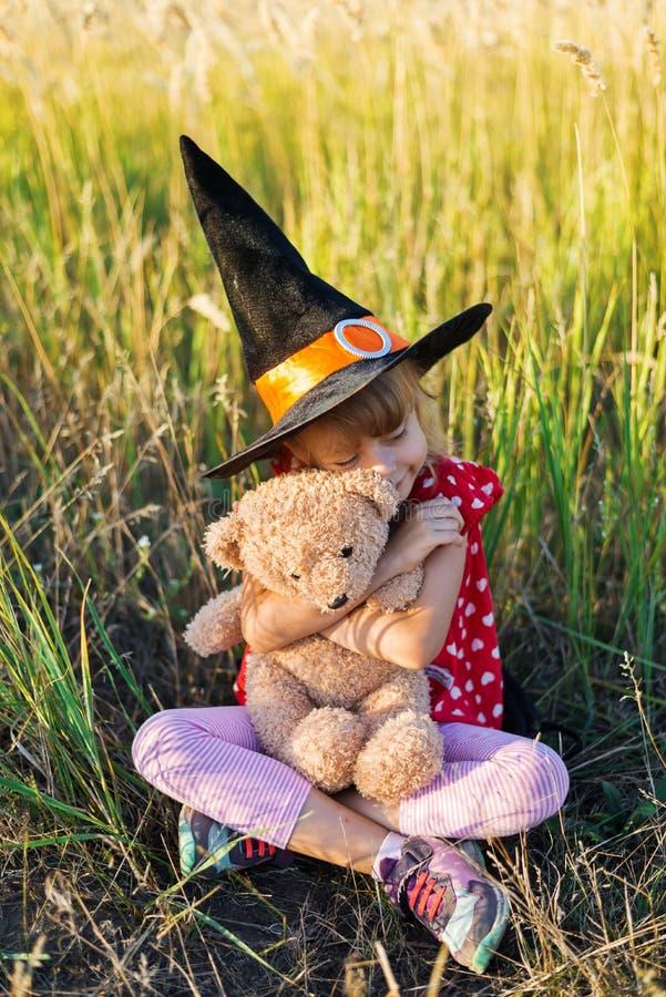 Fundo do feriado de Dia das Bruxas: menina em um chapéu da bruxa que senta-se na grama com um urso de peluche foto de stock royalty free