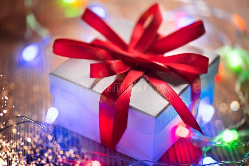 Fundo do feriado do Natal Caixa de presente envolvida com a fita de seda vermelha e festão colorida das luzes sobre o fundo de ma fotos de stock