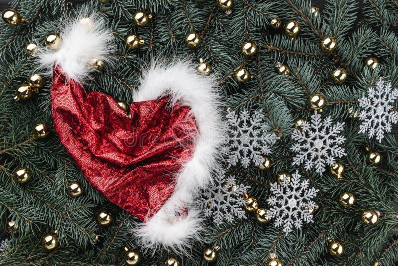 Fundo do inverno de ramos do abeto Decorado com o tampão de Santa dourada das quinquilharias Cartão de Natal Vista superior Felic imagens de stock royalty free