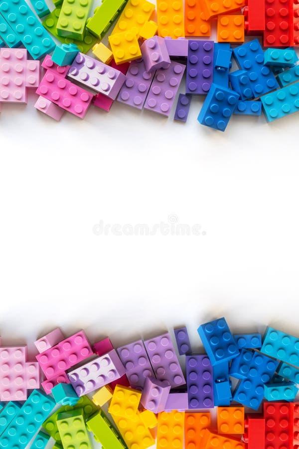 fundo do lego Beira de muitos tijolos coloridos do construtor de Plastick no fundo branco Brinquedos populares Copyspace vertical imagens de stock royalty free