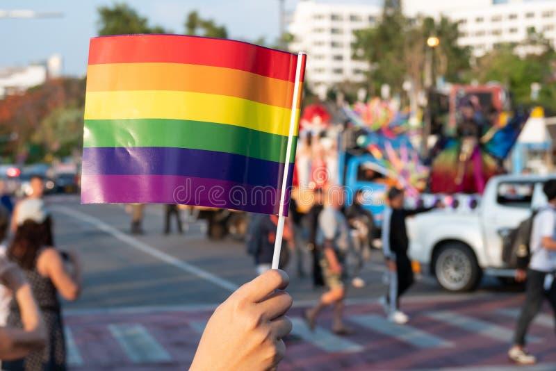 Fundo do mês do orgulho de LGBT um espectador acena uma bandeira alegre do arco-íris no festival da parada de orgulho alegre de L fotos de stock royalty free